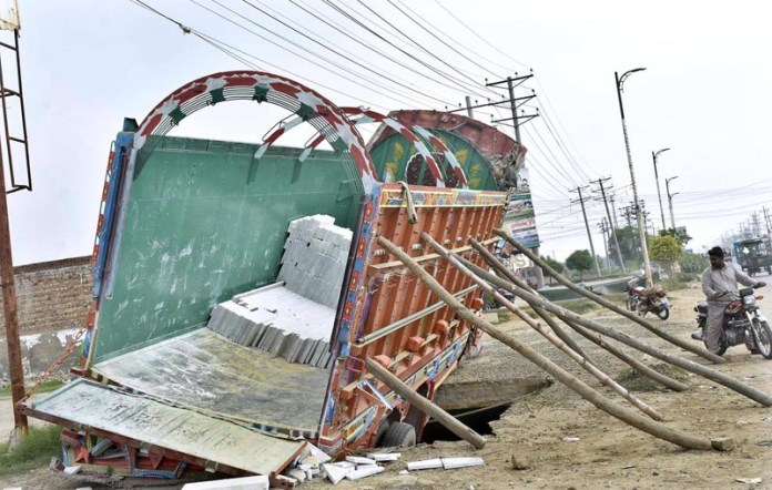 FAISALABAD: September 06 – A view of truck stuck in damaged cover of sewerage nullah at Sitiana Road near Fish Farm. APP photo by Muhammad Waseem
