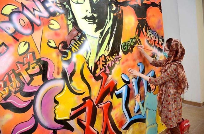 PESHAWAR: September 14 - Student busy in wall painting at SBBWU. APP Photo by Shaheryar Anjum
