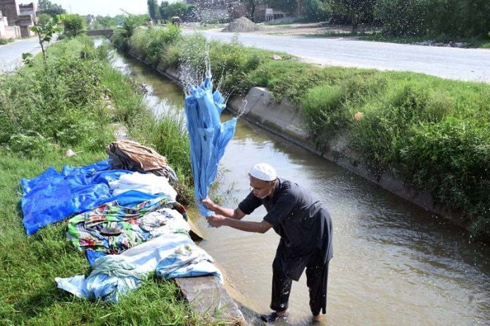 SARGODHA: September 17 - A person washing clothes in water channel. APP photo by Hassan Mahmood