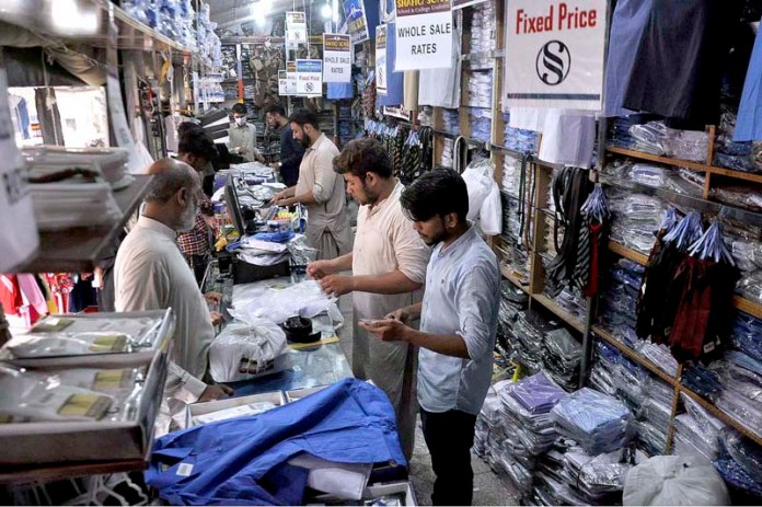 ISLAMABAD: September 13 – People busy in purchasing school uniform for their children at Sunday Bazaar as educational institutions will reopen in phases starting September 15 after COVID-19 pandemic. APP photo by Saleem Rana