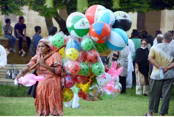 KARACHI: September 05 – A female vendor displaying air filled plastic balls to attract customer at Frere Hall Park. APP Photo by Saeed Qureshi
