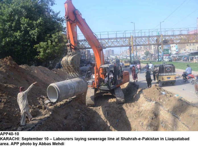 KARACHI: September 10 – Labourers laying sewerage line at Shahrah-e-Pakistan in Liaquatabad area. APP photo by Abbas Mehdi
