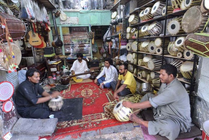RAWALPINDI: September 12 – Workers preparing different musical instruments at their workplace. APP photo by Irfan Mahmood