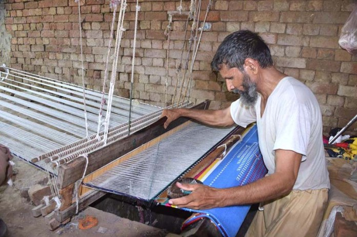 SIALKOT: September 18 - A worker preparing cloth in a traditional way at his workplace. APP Photo by Munir Butt