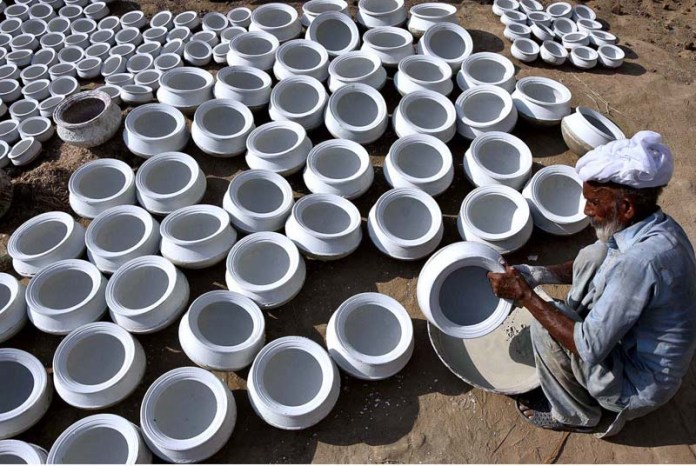 LAHORE: September 17 – An elderly worker busy in coloring the clay made pots after preparing at his workplace. APP photo by Mustafa Lashari