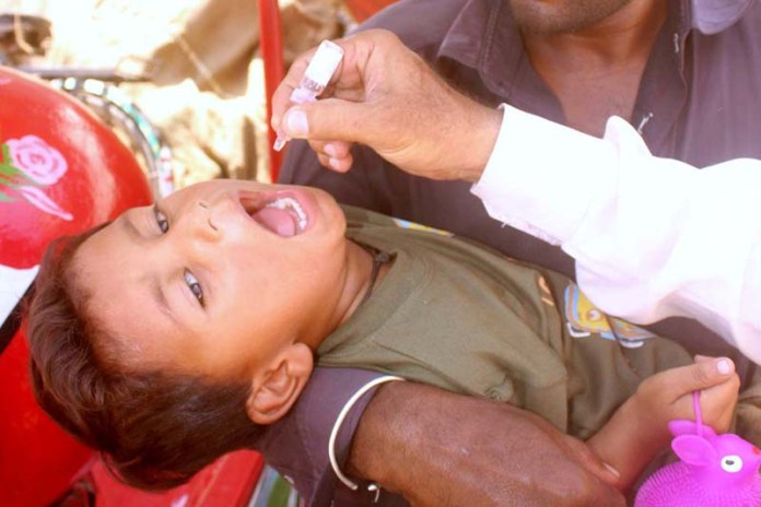 MULTAN: September 21 - Health worker administering polio drops during 5 days of anti polio campaign. APP photo by Tanveer Bukhari