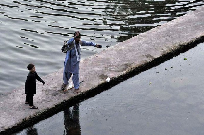 ISLAMABAD: September 18 – A person catching the fishes in a traditional way at Korang Nullah. APP photo by Saleem Rana