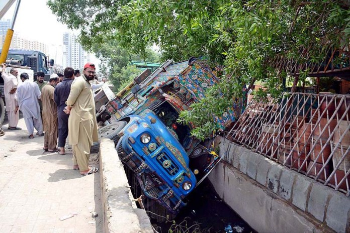 KARACHI: September 02 - Speedy delivery truck fallen in open drain at Korangi Road. APP Photo by Saeed Qureshi