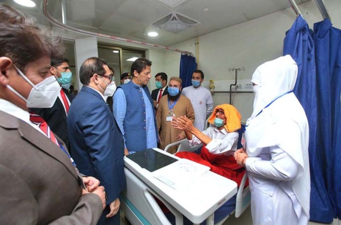 PESHAWAR: September 28 - Prime Minister Imran Khan interacting with a patient at Lady Reading Hospital. APP