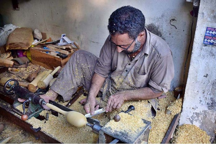 SIALKOT: September 09 - A worker preparing export quality wooden music instruments at his workplace. APP Photo by Munir Butt