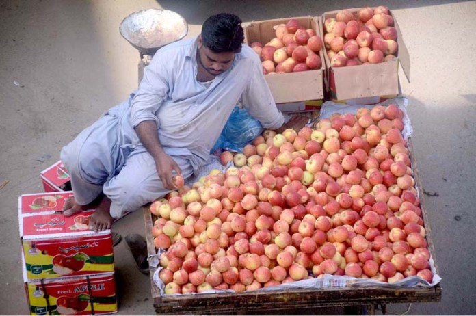 KARACHI: September 07 – A vendor displaying apples to attract the customers on pushcart. APP Photo by Syed Abbas Mehdi