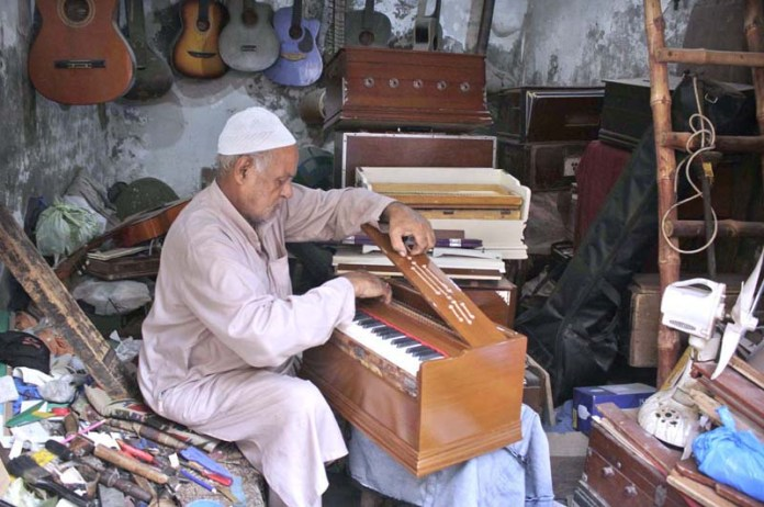 LAHORE: September 10 - An elderly craftsman repairing musical instruments at his workplace. APP photo by Rana Imran