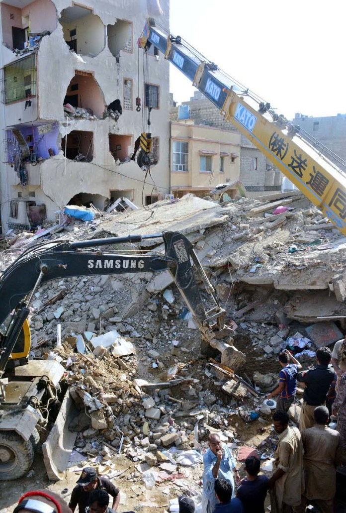 KARACHI: September 10 - A view of rescue operations as a multi-storey residential building collapsed with many people feared trapped under its debris in Allahwala Town at Korangi. APP photo by Saeed Qureshi