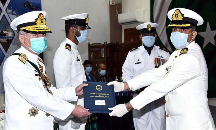KARACHI: September 10 - Chief of the Naval Staff Admiral Zafar Mahmood Abbasi awarding letter of commendation to an officer during PN investiture ceremony. APP