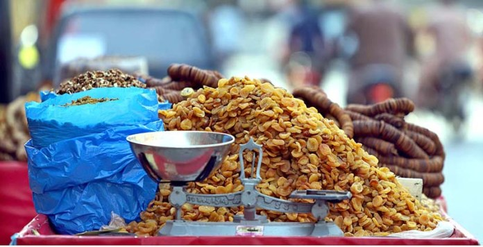 RAWALPINDI: October 20 - A vendor displaying different kind of dry fruits to attract the customers at his roadside setup at Committee Chowk. APP photo by Abid Zia