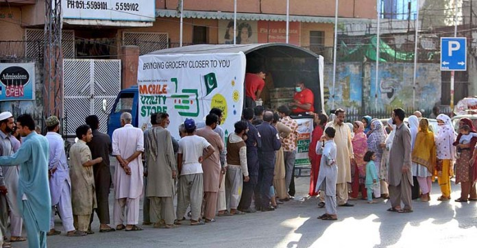 RAWALPINDI: October 21 - A large number of people standing in queue to buy sugar from a mobile utility store at Dhoke Khabba. APP photo by Abid Zia