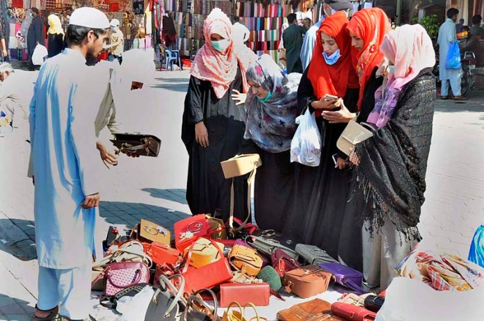 ISLAMABAD: October 18 – Women selecting and purchasing handbags from vendor at stall in Sunday Bazaar. APP photo by Saleem Rana