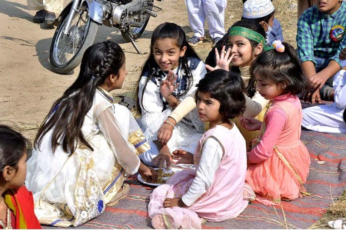ISLAMABAD: October 30 – Children eating food distributed by volunteers to participants of Eid Milad-un-Nabi (PBUH) procession to celebrate birthday of Holy Prophet Muhammad (Peace Be Upon Him). APP photo by Saleem Rana