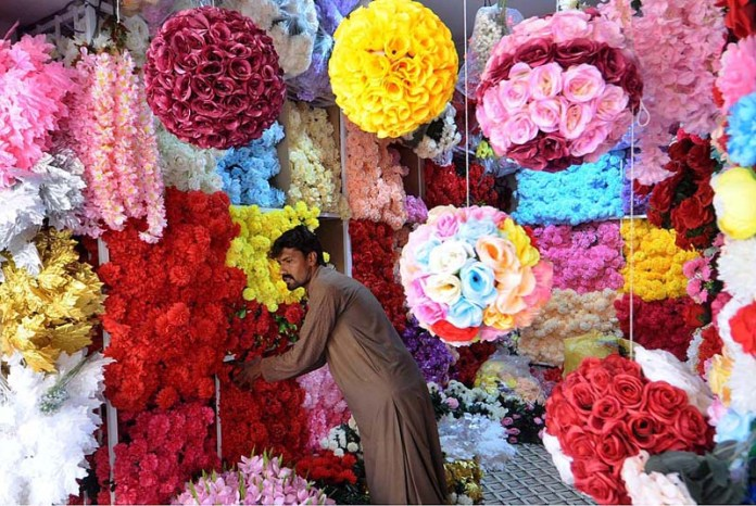RAWALPINDI: October 28 – A vendor arranging and displaying flowers to attract the customers at his shop in a local market of the city. APP photo by Irfan Mahmood