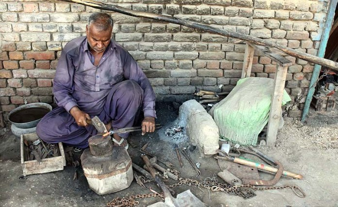 LARKANA: October 03 - A blacksmith repairing iron tools at his workplace near Ratodero. APP photo by Nadeem Akhtar