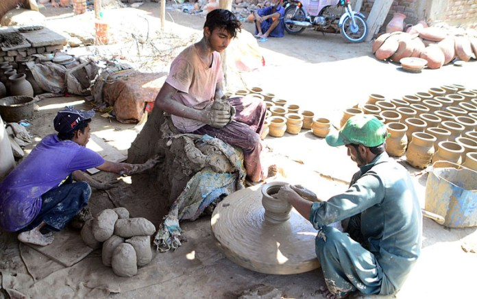 HYDERABAD: October 13 – Labourers preparing clay-made stuff at their workplace. APP photo by Akram Ali