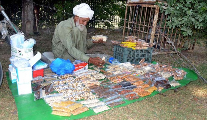 LAHORE: October 14 – An elderly vendor arranging and displaying different food items at his roadside setup. APP photo by Ashraf Ch