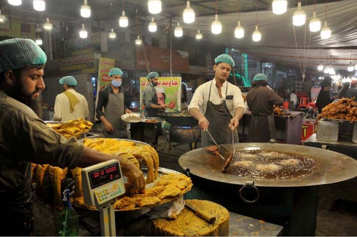 ISLAMABAD: October 18 – Vendors busy in frying fish for customers at their shop in Federal Capital as demand of fish increasing due to changing weather. APP photo by Saeed-ul-Mulk