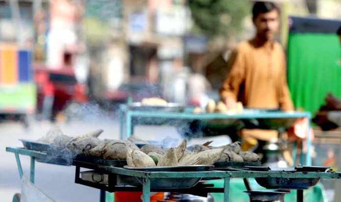 RAWALPINDI: October 19 – A vendor displaying sweet potatoes at his roadside setup at Committee Chowk to attract customers. APP photo by Abid Zia
