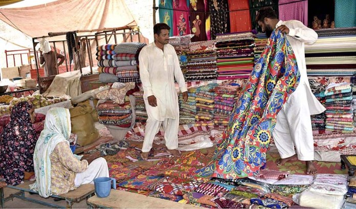FAISALABAD: October 21 - Women purchasing bed sheets displayed by a vendor to attract the customers. APP Photo by Muhammad Waseem