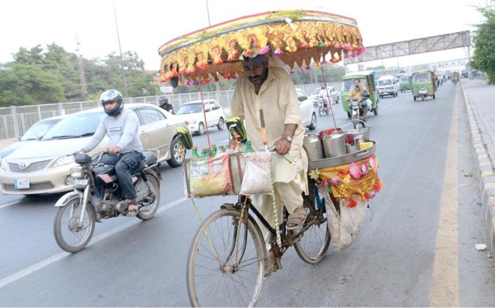 LAHORE: October 19 – A vendor on his way loaded potatoes on his bicycle to attract the customers. APP photo by Amir Khan