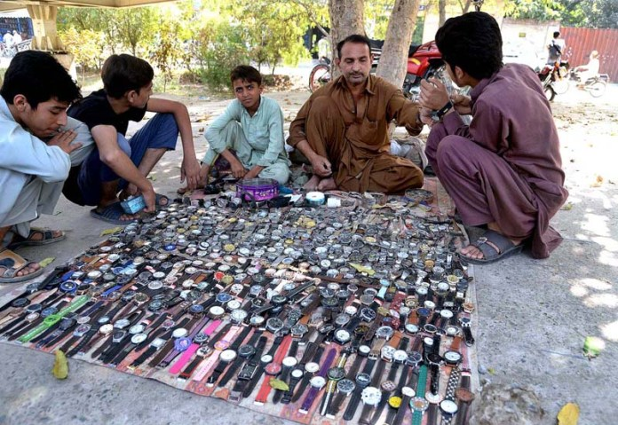 LAHORE: October 11 - A vendor displaying wrist watches to attract the customers at his roadside setup on the sidelines of Canal. APP photo by Amir Khan