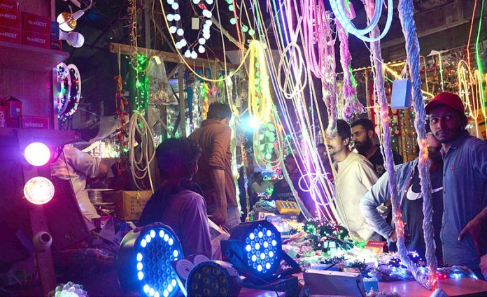 LAHORE: October 20 - People purchasing colourful lights in connection with Eid-e-Milad-un-Nabi (SAWW) celebrations. APP photo by Amir Khan