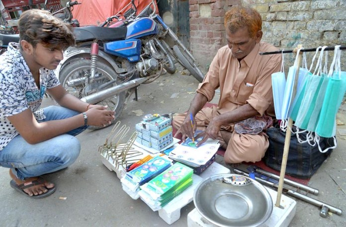 LAHORE: October 19 - A man selling water boats and hand-made drawings at roadside setup. APP photo by Amir Khan