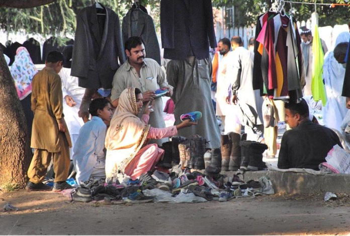 ISLAMABAD: October 18 – Woman selecting children shoes from vendor at Sunday Bazaar. APP photo by Irshad Sheikh