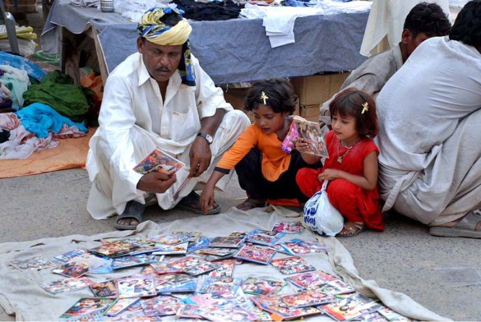 SARGODHA: October 11 - A man purchasing CDs at Urdu Bazar. APP photo by Hassan Mahmood