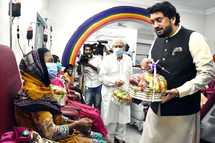 LAHORE: October 06 - Chairman Parliamentary Committee on Kashmir Shehryar Afridi distributing gifts among the thalassemia patients during his visit to Sundas Foundation. APP Photo by Mustafa Lashari