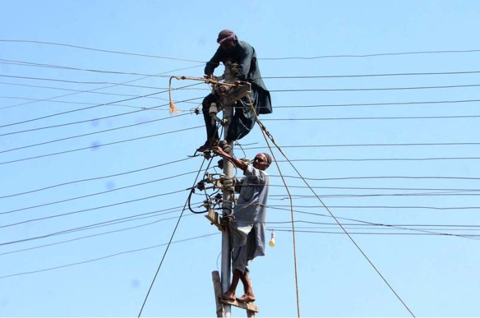 HYDERABAD: October 11 – WAPDA employees busy in repairing the electric cable on the pole at Kotri Railway Station. APP photo by Farhan Khan