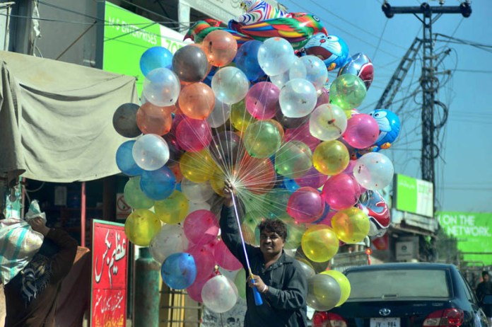 ISLAMABAD: October 06 – A street vendor displaying colourful balloons to attract the customers. APP photo by Irshad Sheikh