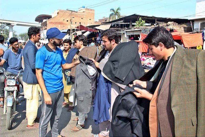 LAHORE: October 27 - People busy in purchasing second hand warm clothes from vendors at Lunda Bazaar. APP photo by Tabasam Naveed