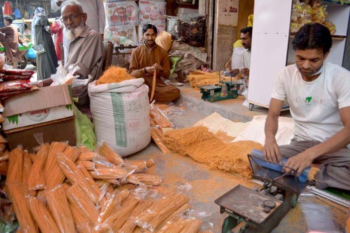 SARGODHA: October 29 – Vendor busy in packing vermicelli in connection with Eid-e-Milad-un-Nabi (SAWW) at urdu bzar. APP photo by Hassan Mahmood