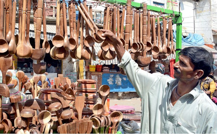 KARACHI: October 06 - A roadside vendor displaying wooden utensils on his hand cart to attract customers at Kala Pul area. APP Photo by Saeed Qureshi