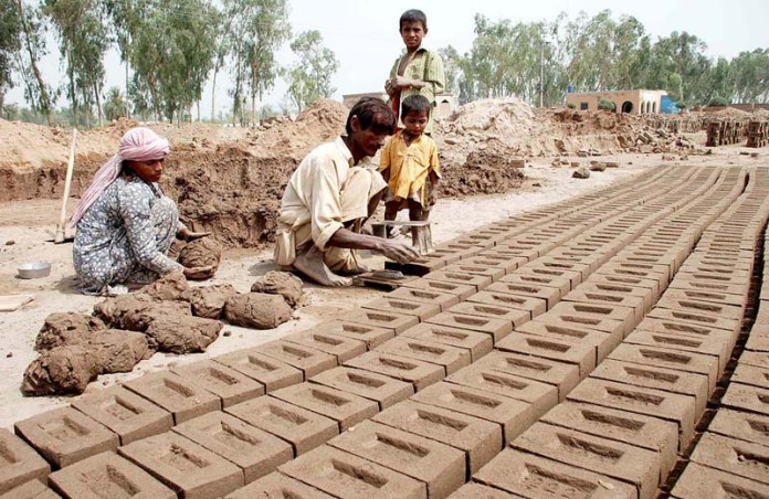 SARGODHA: October 12 – A labourer family busy in making bricks at a local kiln. APP photo by Hassan Mahmood
