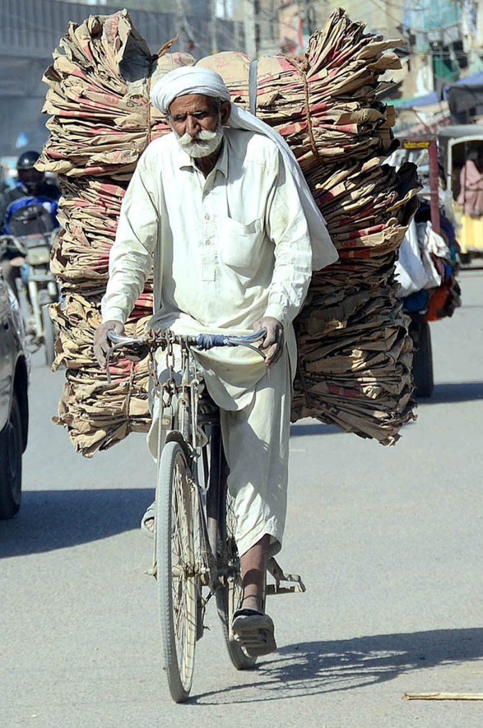 KARACHI: October 21 – An elderly person on the way on his bicycle loaded with empty cement bags after collected from different points in Provincial Capital. APP photo by Abbas Mehdi