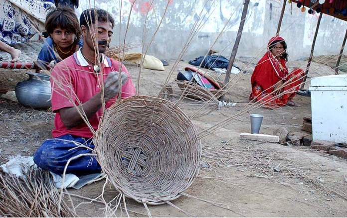 SARGODHA: October 21 - A worker busy in making traditional basket with branches of tree at his setup. APP photo by Hassan Mahmood