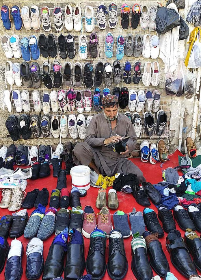 LARKANA: October 28 - A vendor displaying used shoes to attract the customers at Girls College Road. APP photo by Nadeem Akhtar