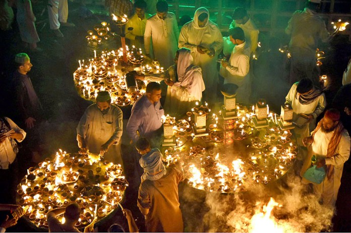 LAHORE: October 06 - Devotees lights-up oil lamps at Data Darbar in connection with 977th Urs celebrations of Data Ali Hajveri as a large number of people arrive to attend the three-day Urs celebrations. APP photo by Mustafa Lashari