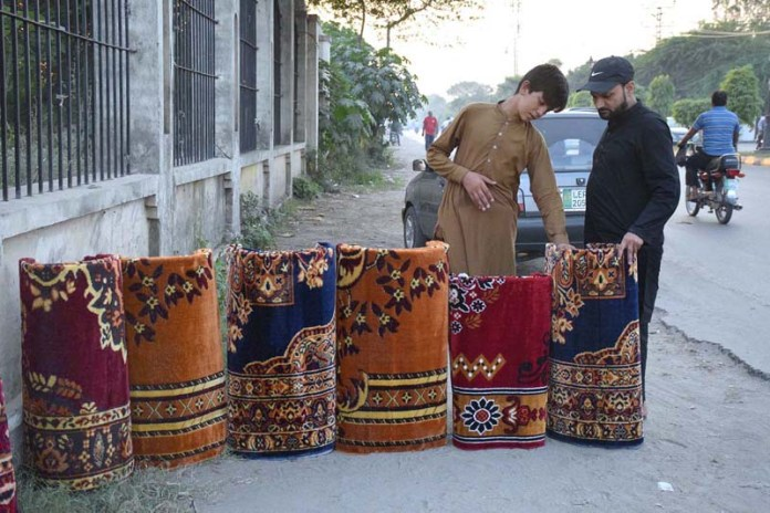 SIALKOT: October 02 - A vendor selling out carpets at his roadside setup. APP Photo by Muhammad Munir Butt
