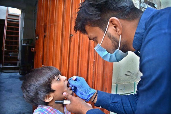 SARGODHA: October 28 - A health worker administering anti polio drops to child at Tewana Park during 5-day Anti-Polio Drive. APP photo by Hassan Mahmood