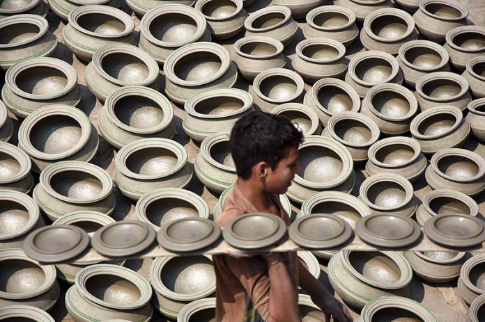 LAHORE: October 15 - A young worker busy in arranging the clay made pots for drying purpose after preparing at his workplace. APP photo by Mustafa Lashari