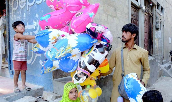 KARACHI: October 19 - A boy keenly looking air filled plastic toys displayed by vendor at one of the street of lines area in Provincial Capital. APP photo by M Saeed Qureshi